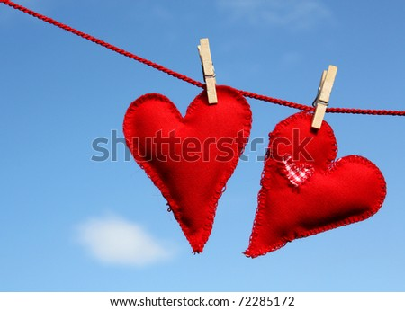 Two homemade hearts on line in front of blue sky