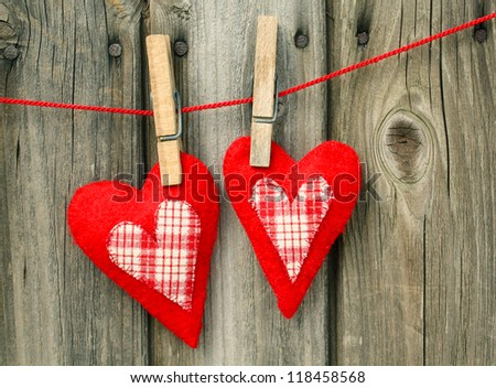 two homemade red hearts made of felt and plaid cloth - stock photo