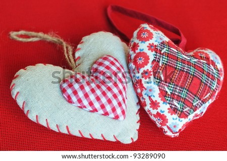 Two homemade sewn hearts on red background