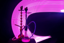 two hookahs with shisha coals pink neon lighting on a dark background