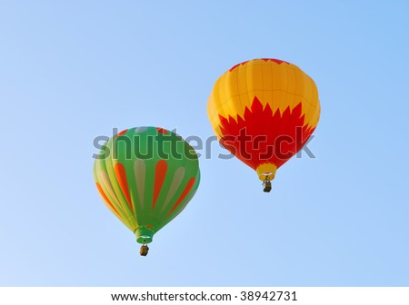 Two hot air balloons against a blue sky