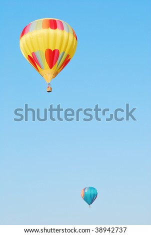 Two hot air balloons against a blue sky - vertical