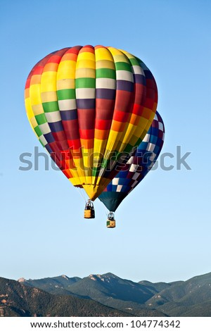 Two hot air balloons ascend over front range mountains during Colorado Springs' 2011 Balloon Classic
