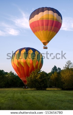 Two hot-air balloons taking off or landing in a field. One is on the ground. The other is airborne.
