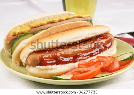Two hot dogs with ketchup and mustard and salad