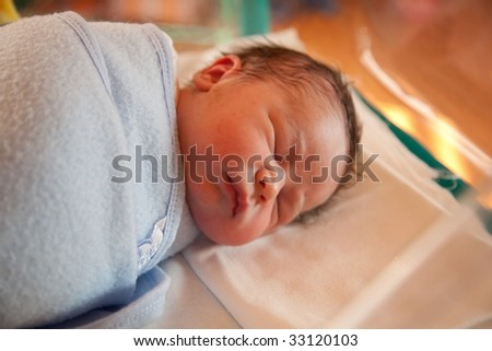 Two hours old baby resting in swaddling-clothes