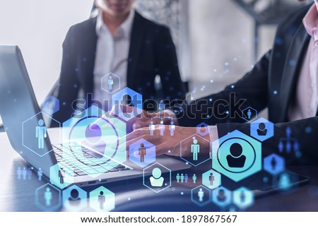 Two HR specialists in formal wear analyzing the recruitment market using laptop to boost the intern program at international consulting company. Social networking hologram icons.
