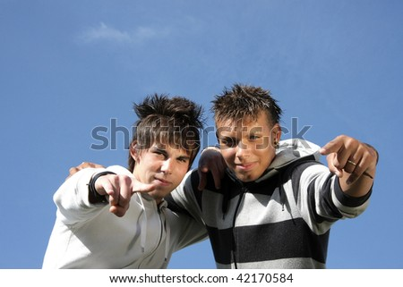 two hugging teenage friends pointing with their fingers towards camera, photographed in the summer sun with blue sky and tiny clouds in the background