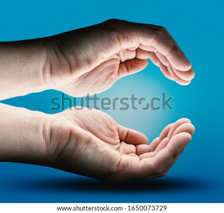 Two Human Hands with Empty Space on Blue Background. Energy - Light and Power Concept. Future Product Presentation.