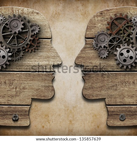 Two human head silhouettes with cogs and gears