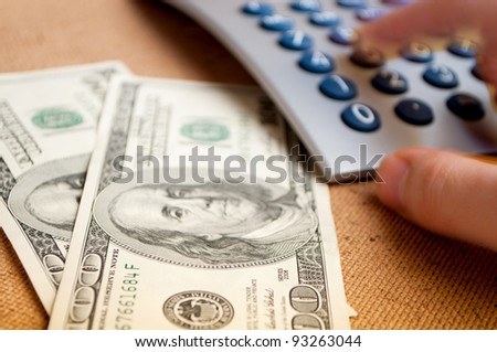 Two hundred-Dollar bills and male hand in motion, pressing keys on the calculator