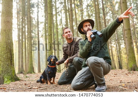 Two hunters with binoculars and with hound as hound on the stalk in the forest #1470774053
