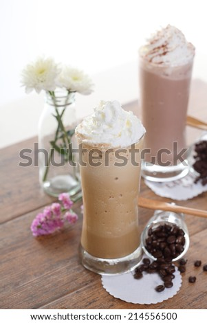 two Ice coffee with flower and coffee beans on a wood table