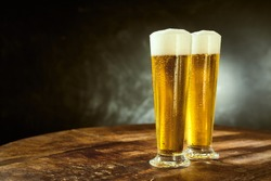 Two ice cold frothy beers in elegant long glasses standing on an old rustic wooden table in a pub, bar or tavern with copy space on a slate background