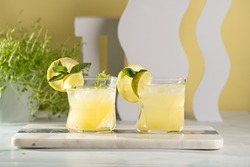 Two ice lemonade drinks in irregular glass with lime pieces and mint