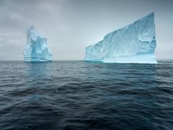 two icebergs in dark water in Antarctica