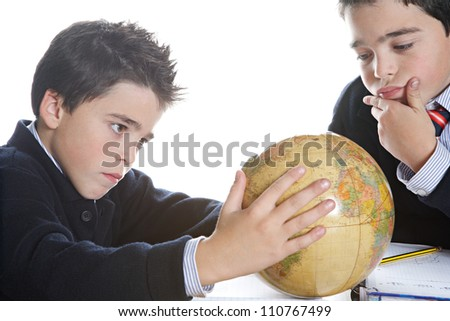 Two identical twin brothers doing their geography homework, looking at a world globe while sitting on a wooden table at home.