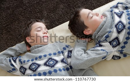 Two identical twin brothers sleeping on a white leather couch while wearing identical jumpers.