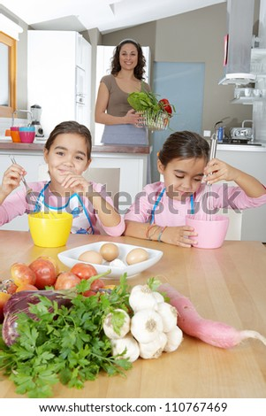 Two identical twin sisters beating eggs in their home kitchen while on vacations, while their mother stands behind them.