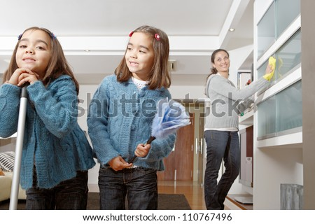 Two identical twin sisters cleaning their home living room while on vacations, while their mother dusts cabinets behind them.