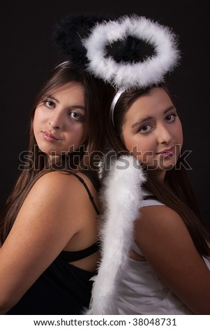 Two identical twin sisters wearing white and black angel halos posing together over black