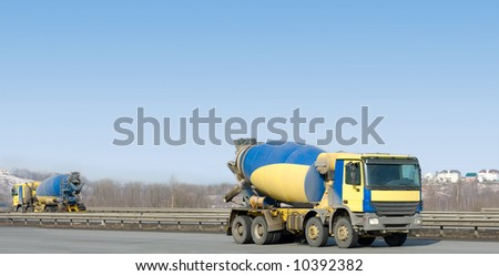 "two identical  yellow concrete mixer trucks drive in different directions  - See similar images of this ""Business vehicles"" series in my portfolio"