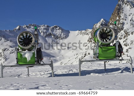 Two idle snowcannons in front of mountains and blue sky