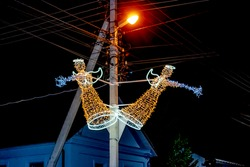 Two illuminated sculptures of angels on an electric pole on Kanatna Street in Kherson (Ukraine). Night lighting and decoration of city street