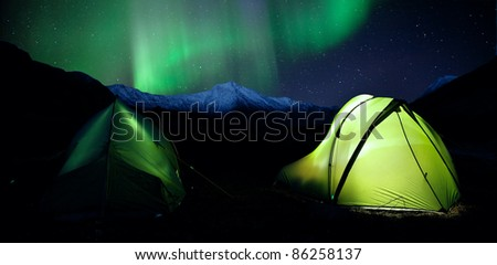 two illuminated Tents under Northern Lights in the Mountains of Sweden