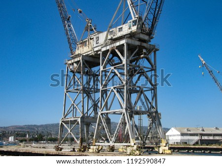 Two inactive mobile gantry cranes, in an old ship yard. They loaded and unloaded cargo from ships at a port of the Pacific Ocean.