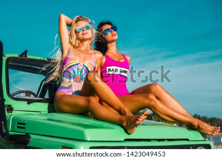 Two incredible beautiful young girls in bikini swimsuits, traveling around a tropical island in a cabriolet off-road car, summer vacation