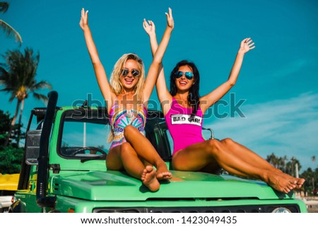Two incredible beautiful young girls tan in bikini swimsuits, traveling around a tropical island in a cabriolet off-road car, summer vacation