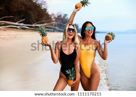two incredibly beautiful sexy girl models in a bikini on the sea shore of a tropical island, blonde brunette, bronze tan, travel summer vacation, fashion style