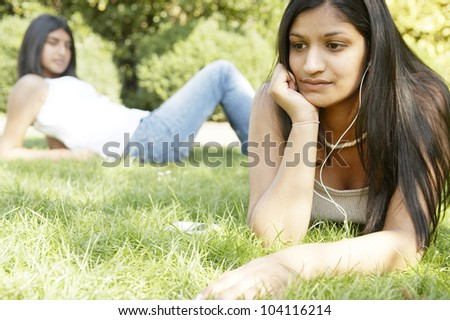 Two indian girls in the park using technology and listening to music.