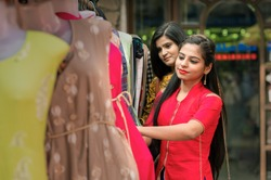Two Indian Women shopping choosing dresses. Beautiful young shoppers in clothing store in India.