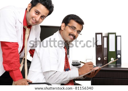 Two Indian young doctor in hospital computer desk isolated on white