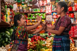 Two indigenous  girls playing clapping game in a grocery store of Guatemala.