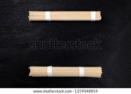 Two individually wrapped portions of udon noodles, shot from above on a black background with a place for text