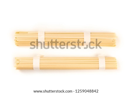Two individually wrapped portions of udon noodles, shot from above on a white background with a place for text