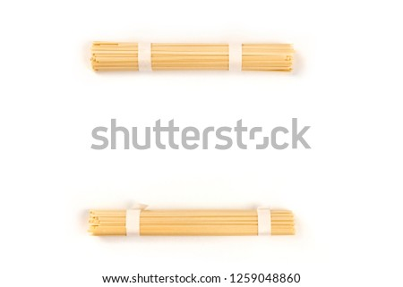 Two individually wrapped portions of udon noodles, shot from the top, forming a frame on a white background with copy space