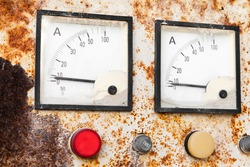 Two industrial square ammeters show zero power level, close up photo of a rusty old electric control panel