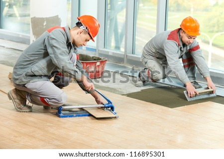 Two industrial tiler builder worker installing floor tile at repair renovation work - stock photo