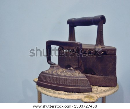 two iron irons stand on a chair nearby #1303727458