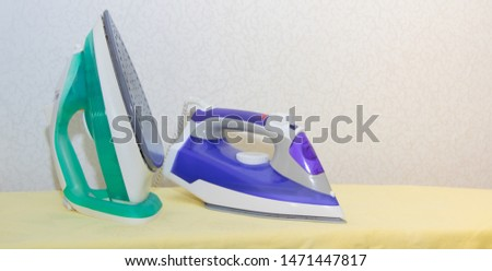 Two irons on an ironing board. Selection and comparison of irons. Ironing board.