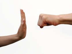 Two isolated human hands: a man's hand in threatening movement with fist and a woman's hand in stopping gesture in white background. Stop violence and abuse. Concept of gender of domestic violence.