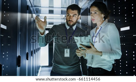 Two IT Engineers in Data Center / Server Room, Talking, one of them Pointing Forward, Other Holds Tablet Computer. #661114456