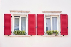 Two Italian windows on the white wall facade with open red color classic shutters and flowers on the windowsill