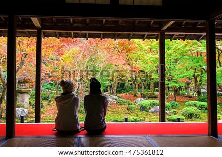 Two Japanese girls enjoy Autumn colorful Japanese garden at Enkoji temple in Kyoto, Japan. Here is the Rinzai Zen Sect and very famous during fall colors in Autumn.