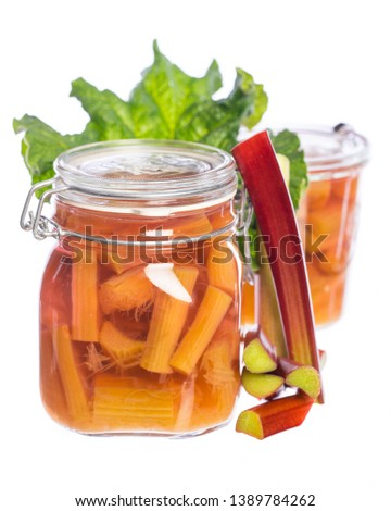 two jars with rhubarb compote and rhubarb leaf on white background