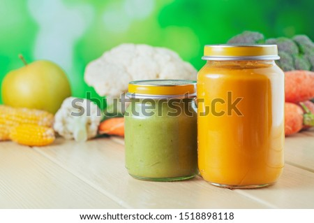 Two jars with vegetable puree on the light wooden background. Selective focus. #1518898118